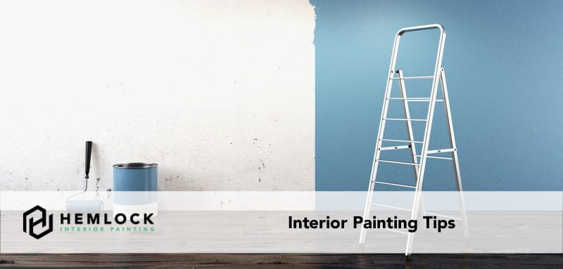 featured image interior painting tips ladder, paint bucket and roller against a partly painted wall