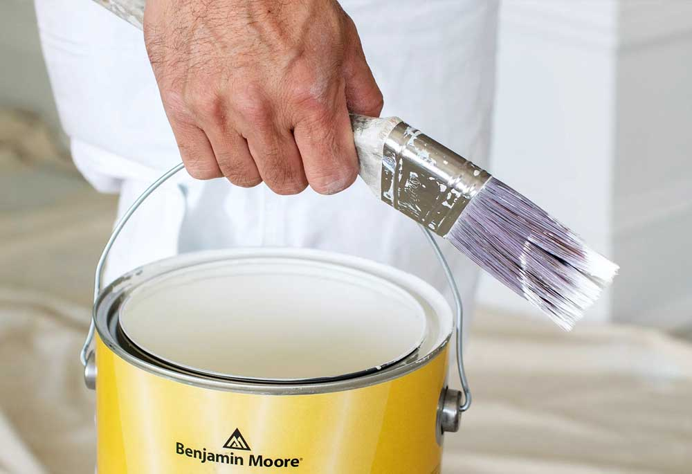 A bucket of high-quality paint from Benjamin Moore that will be used on the exterior of the house.