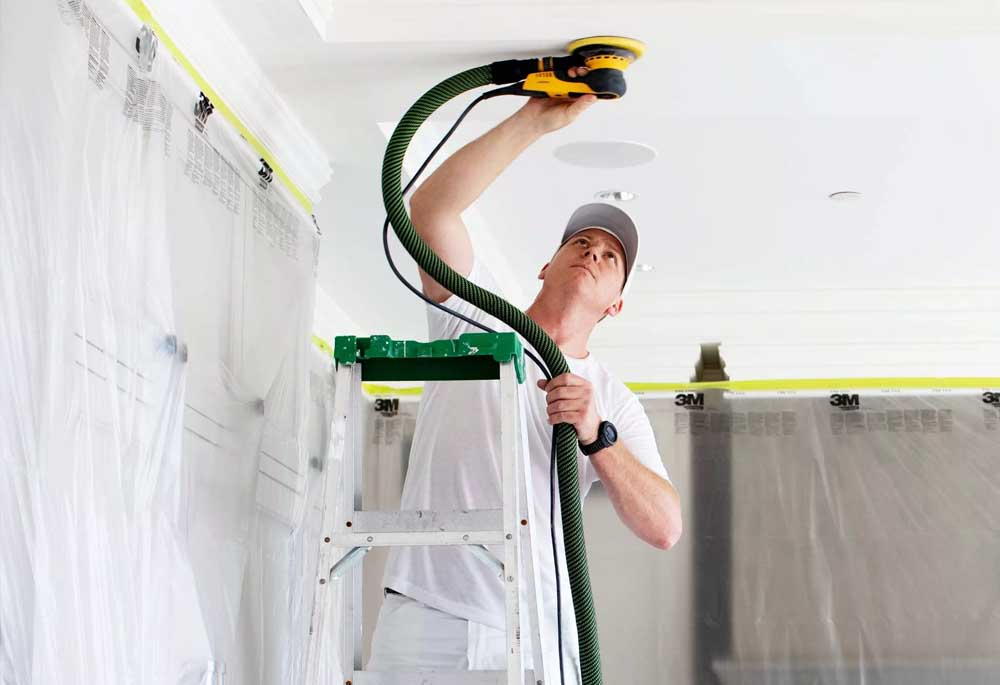 A Hemlock painter uses a dustless sanding machine to prepare surfaces for interior painting.