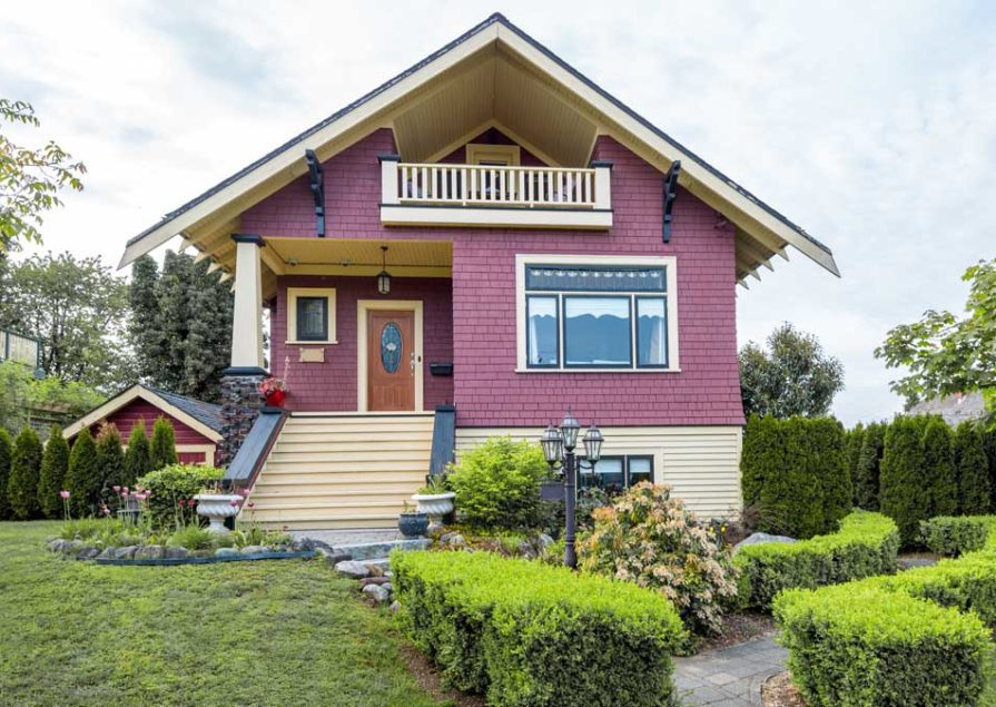 A red house that has been expertly painted, with light wood accents, by Hemlock Painting.