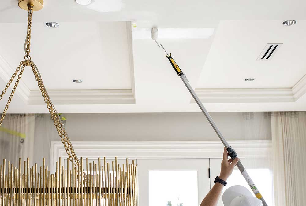 A Hemlock Painting employee expertly paints a ceiling white; we are proud to provide the best in interior house painting services.